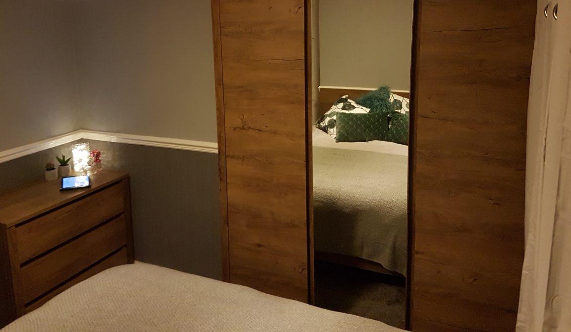King size bed from JYSK seen in a wardrobe door mirror