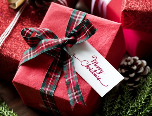 A pile of presents wrapped in red gift wrap and tartan bows