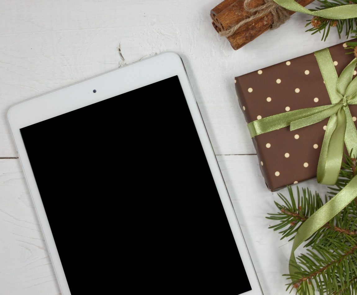 ipad tablet on a white background with brown Christmas present next to it