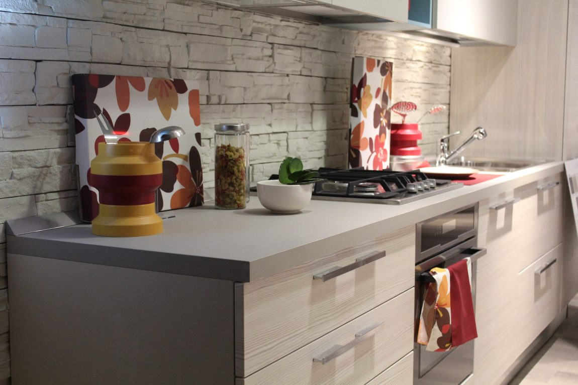 A modern white kitchen unit with a built in oven and hob