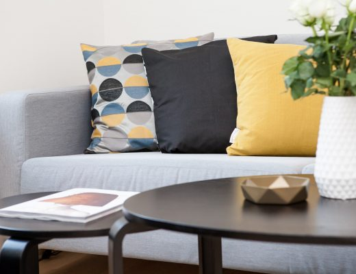 a grey sofa with 3 colourful cushions on it set begins a black coffee table. on the table is a white vase with flowers in it.