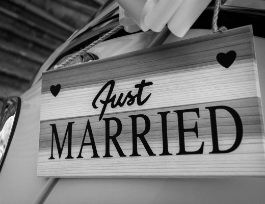 Black and white photograph of a sign on a wedding car saying just married