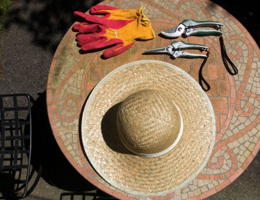 a straw hat, gardening gloves and small shears sat on top of a garden table