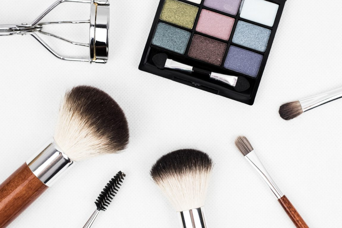 a selection of makeup brushes and an eye shadow palette