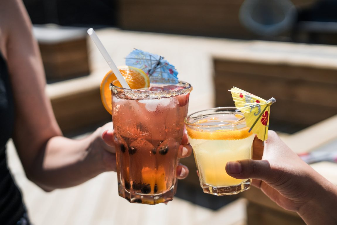 two women drinking alcoholic cocktail drinks