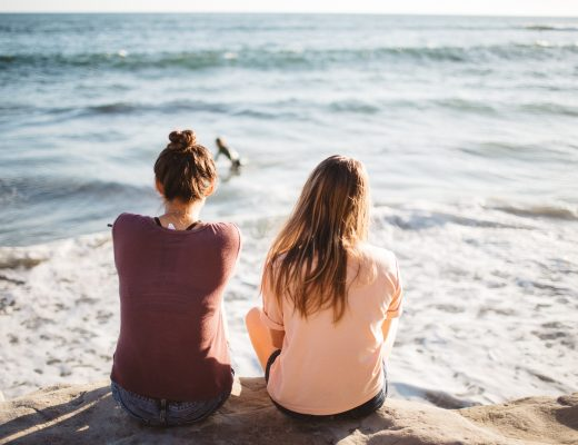 two women sitting on the beach looking out to sea