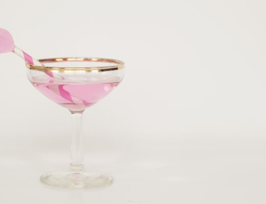 A pink alcoholic drink in a glass with a gold rim, it has a pink striped straw with a heart on top of it
