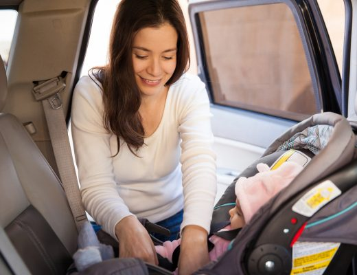 Young mum securing a child car seat