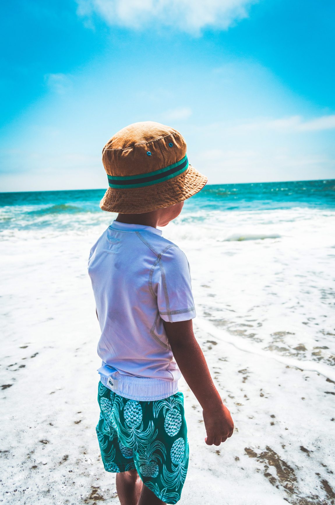 a small boy stood on the beach on a summer day. He is wearing a white tshirt, green shorts and a sun hat