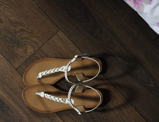 a pair of white sandals on a wooden floor