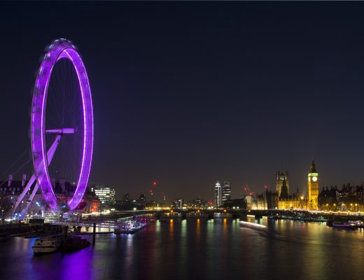London skyline at night. Houses of Parliament is lit up across the river Thames and the London Eye is lit up purple