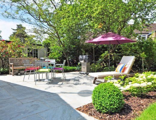 A beige garden chaise long set up under a pink parasol in a sunny garden