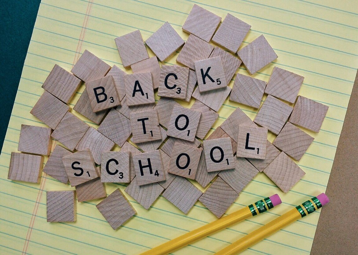 Back to school written in scrabble pieces on top of a yellow piece of paper