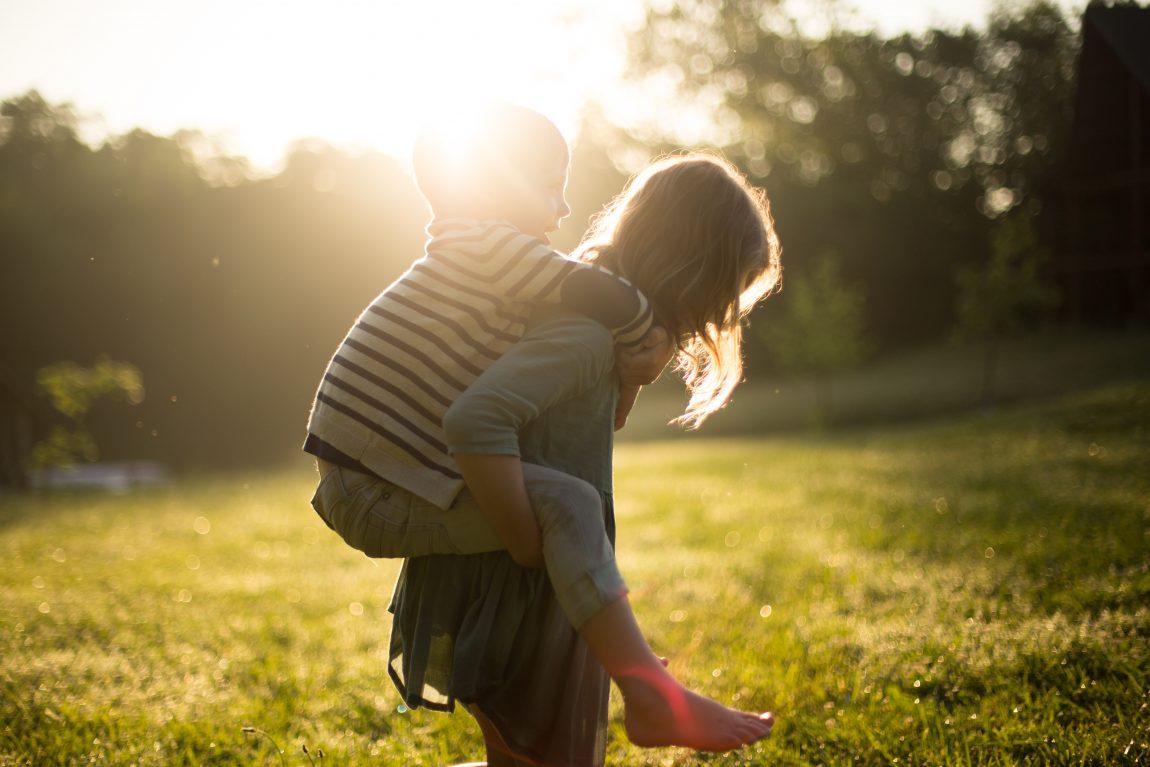 two children playing piggybacks in the garden in the summer