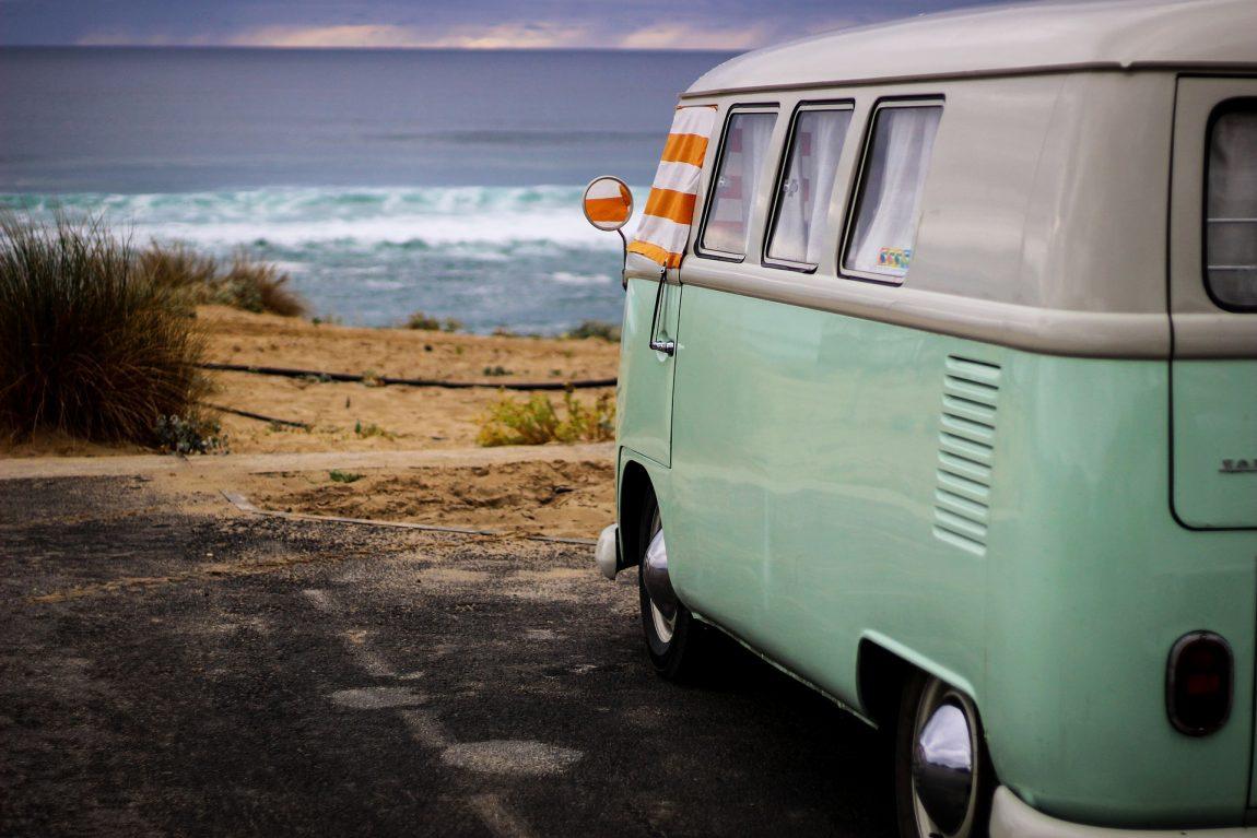 Green VW campervan parked near the beach