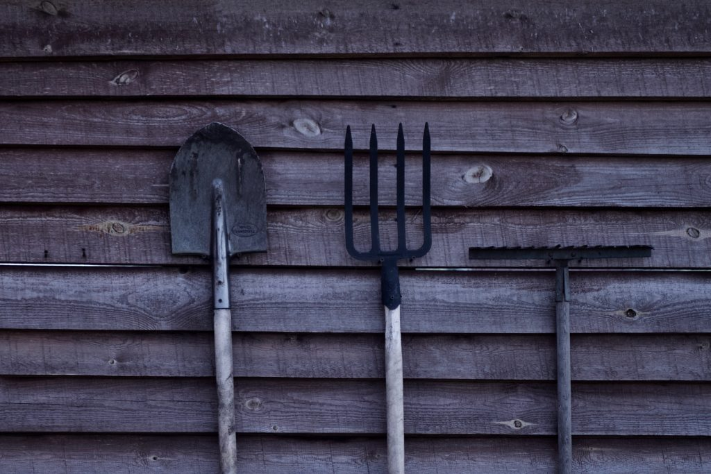 a spade, fork and rake against a brown shred wall