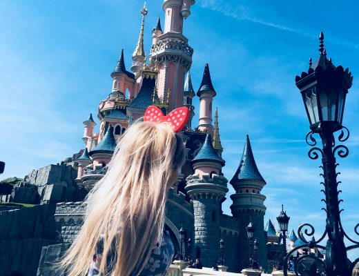 a girl with minnie mouse ears stood in front of the Disneyland castle