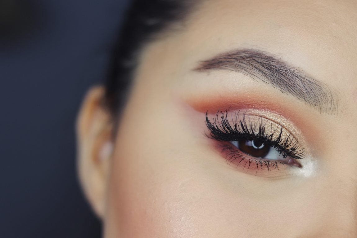 a woman's eye. she is wearing bronze eye shadow with a smokey effect