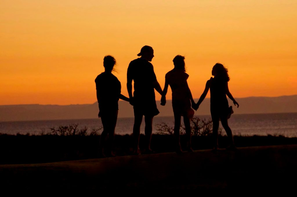 a family holding hands at sunset