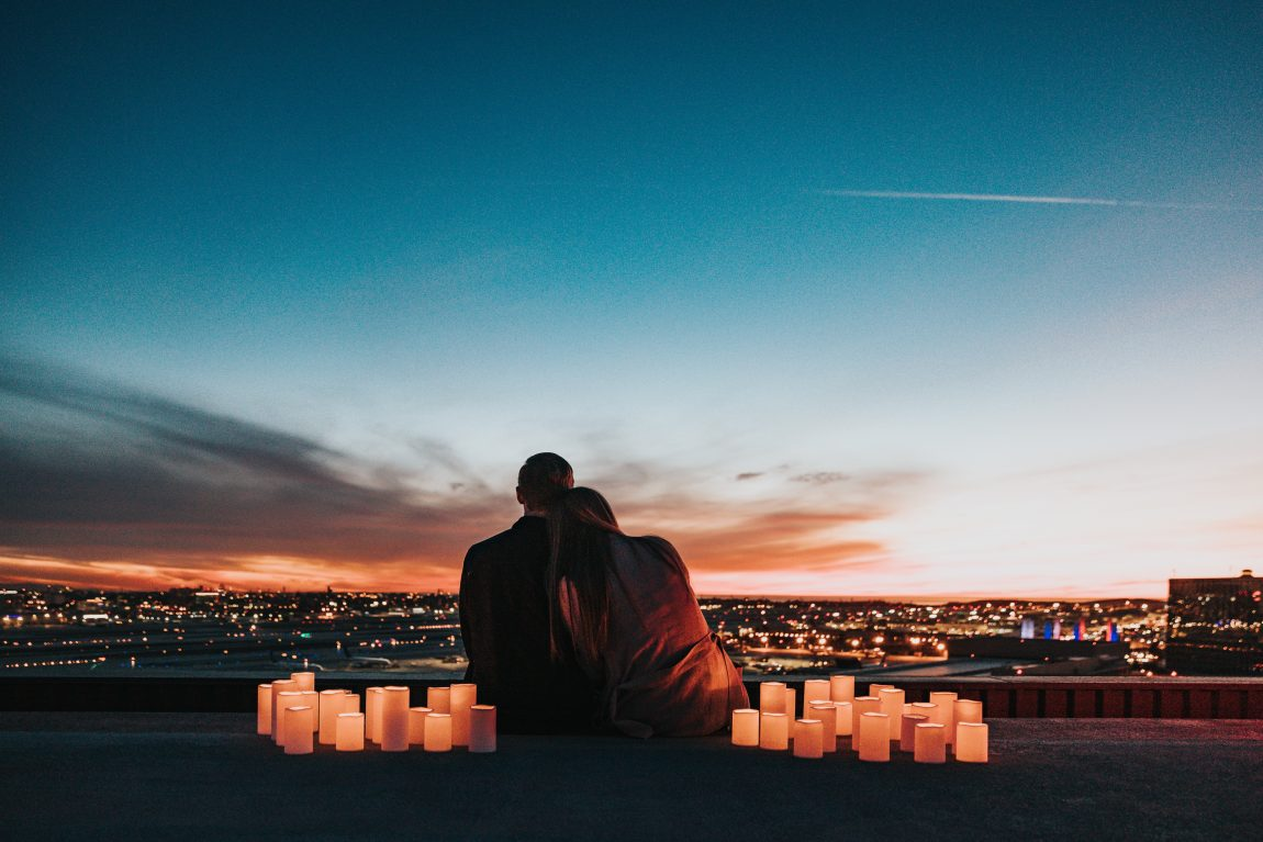 couple sat overlooking a town at night surrounded by candles