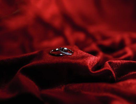 wedding rings sat on a piece of red velvet