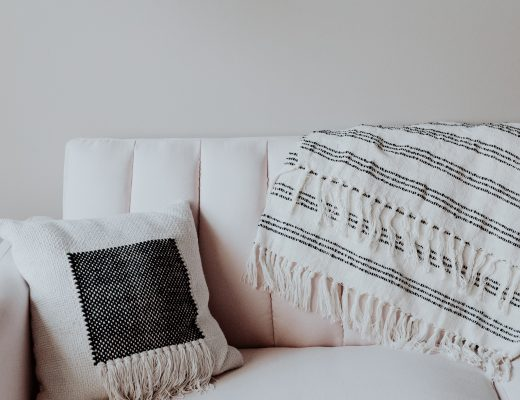 a cushion on a cream sofa with a grey and white throw on the back