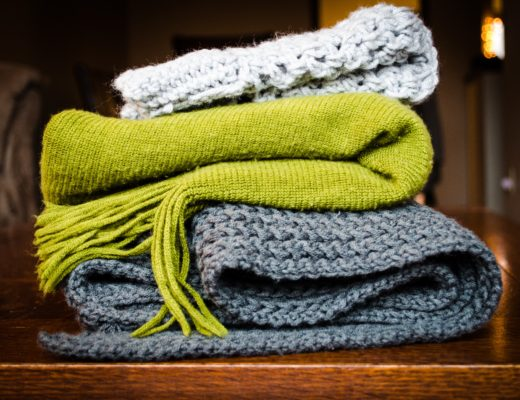 three scarves - one white, one lime green and one grey on a table