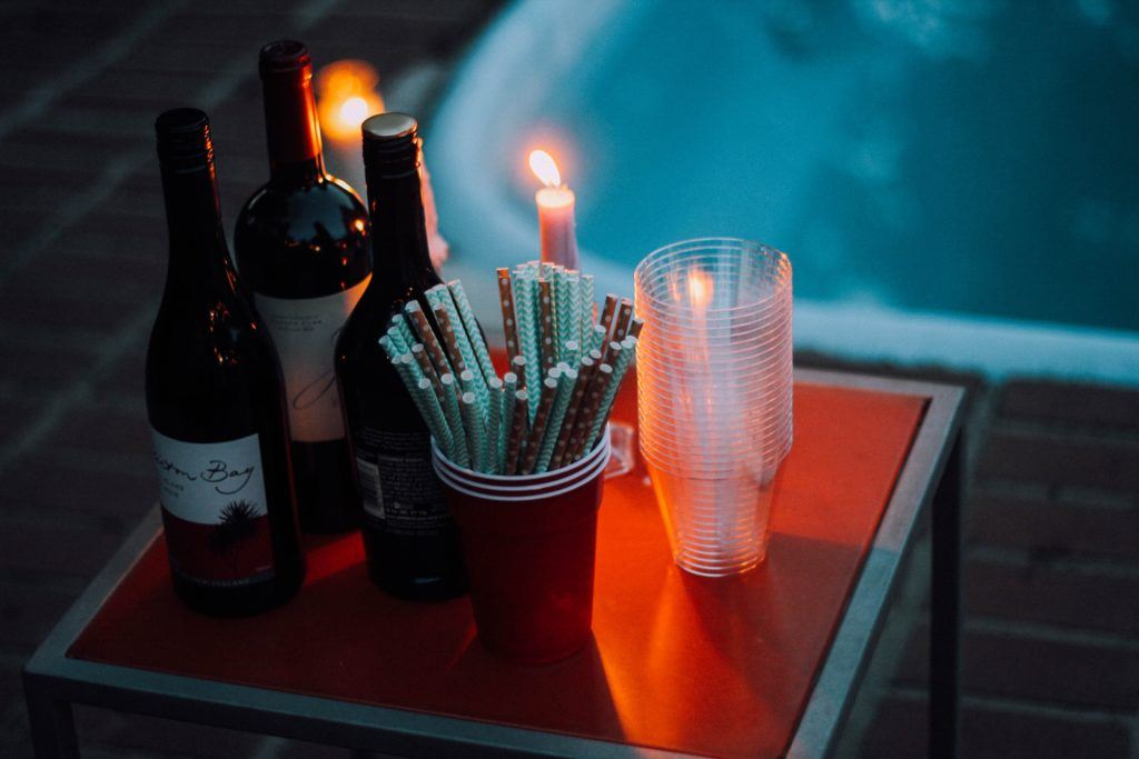 a hot tub in the dark, with a candle and three bottles of wine on the side