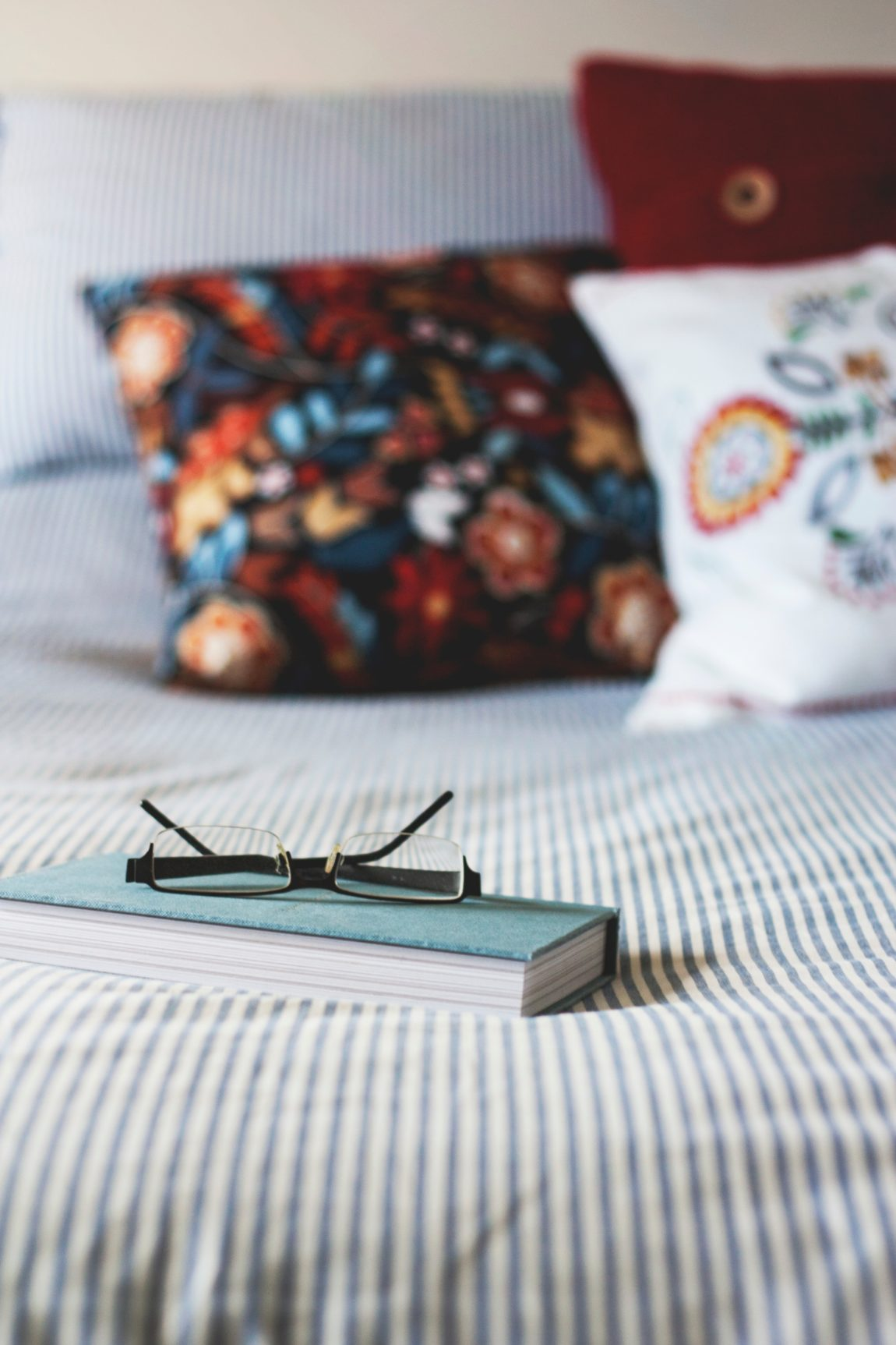 a book sat on a bed with a pair of glasses on top