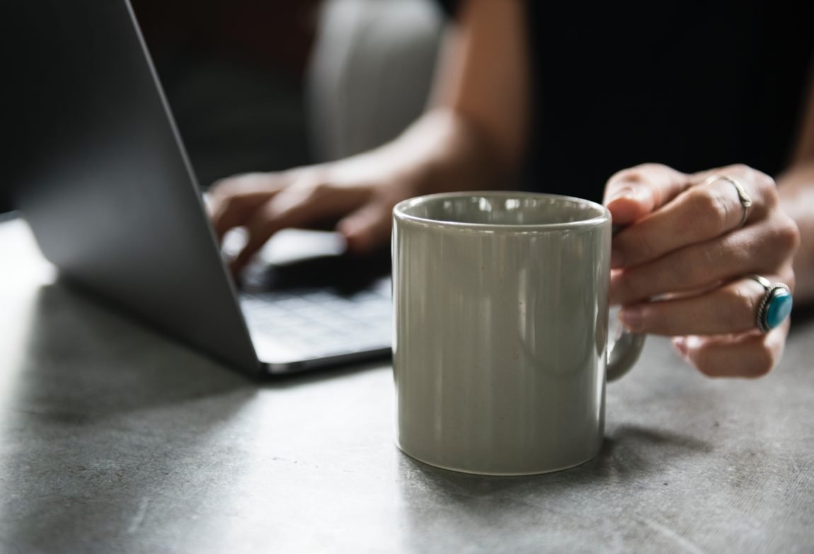 woman sat at a table workin on her laptop reaching for a white mug